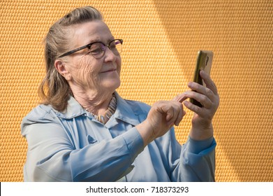 portrait of old lady, grandmother makes selfie outdoors at sun day. modern caucasian granny finger  touch the touchscreen her phone. she has smartphone in her adult hand. technology lifestyle