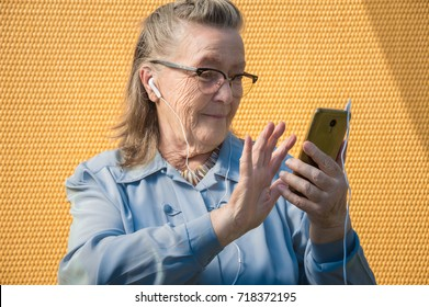 portrait of old lady, grandmother in shock. outdoors at sun day. modern caucasian granny in glasses listening music in headphone, earphones, headphones from phone. she has smartphone in her adult hand