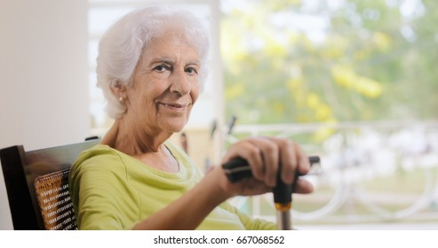 Portrait of old lady sitting on rocker at home. Happy elderly woman relaxing on rocking chair and holding walking stick. Copy space