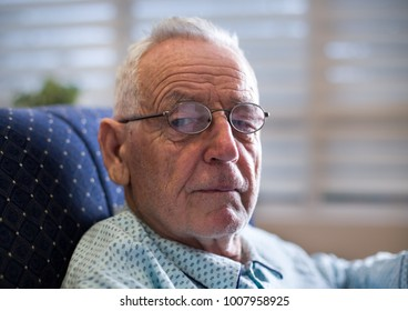 Portrait of old man in 80's sitting on sofa in pajamas, wearing reading glasses and looking at camera