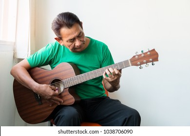 Portrait of old man with acoustic guitar with happiness retirement, on chair at home.