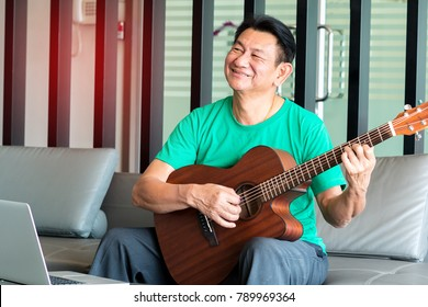Portrait of old man with acoustic guitar with happiness retirement, on chair in room, concept music therapy.