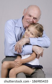 Portrait of an old man eighty years old, on the lap of a man sitting granddaughter four years. Man hugging a girl