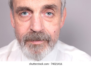 Portrait of old man isolated against grey background.