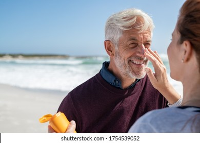 Portrait of old man looking at his mature wife applying sunscreen on nose. Senior husband enjoying vacation with woman while applying sunscreen on face at beach. Middle aged retired couple at sea.