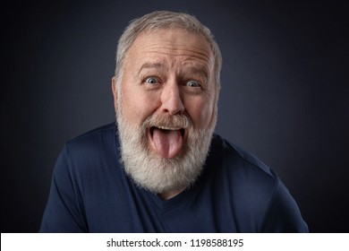 Portrait of an old man making a nasty grimace and pulling the tongue out