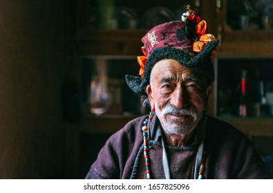Portrait of an old man in typical tibetan clothes inside his house in Ladakh, Kashmir, India.