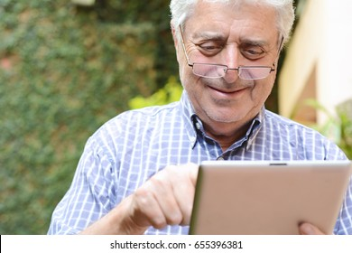 Portrait of an old man using digital tablet. Outdoors.