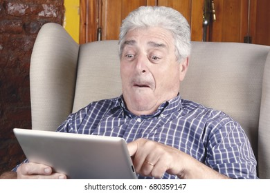 Portrait of an old man using digital tablet and sitting on couch. Indoors.