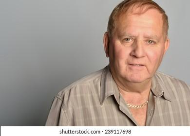 portrait of an old man wearing a beige shirt