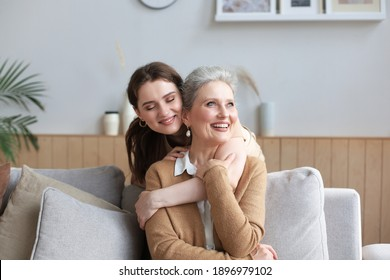 Portrait of old mother and mature daughter hugging at home. Happy senior mom and adult daughter embracing with love on sofa