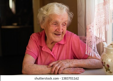 Portrait of an old pensioner woman sitting at a table in the kitchen in her house