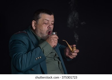 Portrait of an old retired military man who is ready to drink glass of vodka while smoking tobacco-pipe