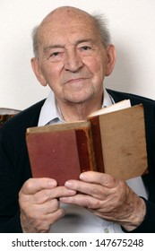 Portrait of an old senior man reading a book