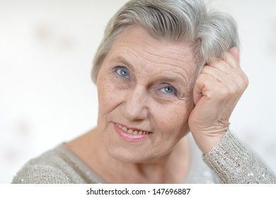 Portrait of an old woman in a gray sweater at home
