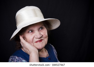 Portrait of the old woman in a hat on a black background