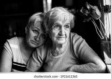 Portrait of an old woman with her adult daughter. Black and white photo.