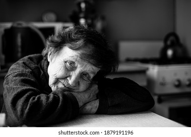 Portrait of old woman in her home. Black and white photo.