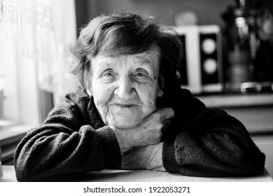 Portrait of an old woman in her home. Black and white photo.