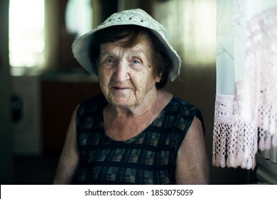 Portrait of an old woman in the kitchen of her house.