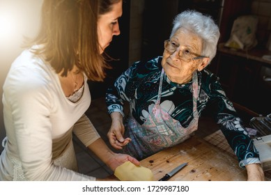 Portrait of old woman kneading dough in a wooden cutting board in her kitchen. Preparing traditional food.