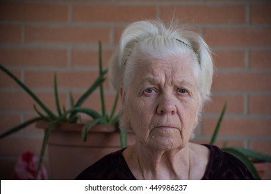 Portrait of old woman on a brick blurred background