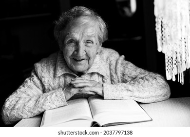 Portrait of an old woman reading a book. Black and white photo.