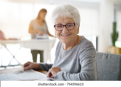 Portrait of old woman reading newspaper while homehelp irons
