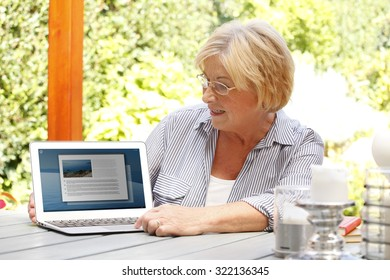 Portrait of old woman sitting at home in the garden in front of laptop and showing something on the screen while surfing on internet.
