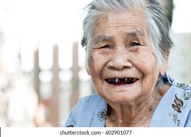 Portrait of old woman is smiling with camera and see  her black tooth