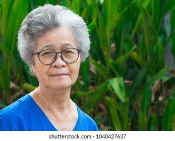 Portrait of a old woman standing and wearing eyeglasses in the garden.