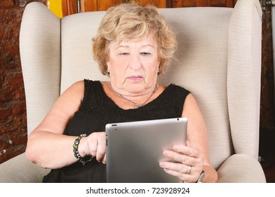 Portrait of an old woman using digital tablet and sitting on couch. Indoors.