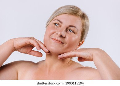 Portrait of an old woman who quite touches the delicate and clean skin of her face with her hands on a white background.