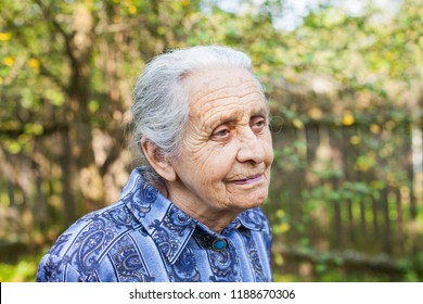 Portrait of old wrinkled lady wearing blue dress, walking in the garden on summertime