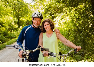 Portrait of older couple bicyclists; lush summer foliage in background