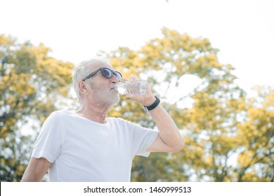 portrait of a older man drinking a water in park after exercies in morning
