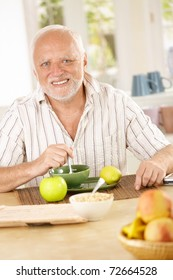 Portrait of older man having morning tea in kitchen, looking at camera, smiling.?