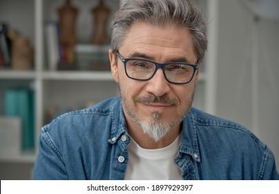 Portrait of older man at home, looking at camera. Happy smile, grey hair, beard, glasses.