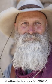 Portrait of an older man with a long white beard and cowboy hat smiling towards the camera. Vertical shot.