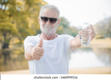portrait of a older man show thumbs up for drinking a water is best after exercies in morning, water good for health concept