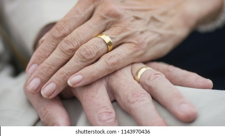 Portrait of older senior hands with wedding rings on