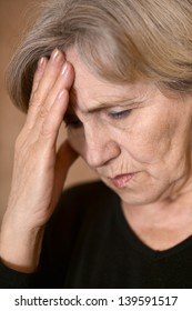 portrait of an older woman with a headache on a beige background