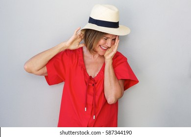 Portrait of older woman laughing with hat against gray wall