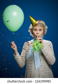 Portrait of older woman with noisemaker, balloon and party hat