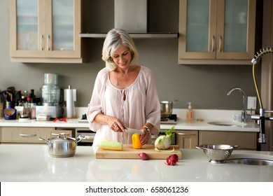 Portrait of older woman preparing food for a meal in kitchen