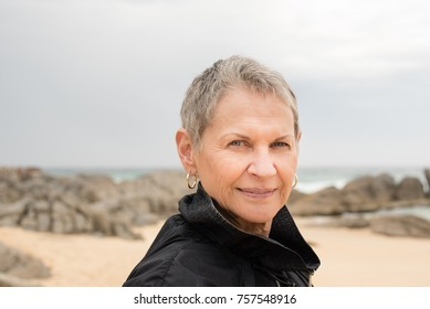 Portrait of older woman with short grey hair at beach on winter's day (selective focus)