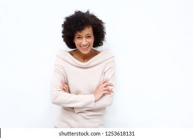 Portrait of older woman smiling with arms crossed against white background