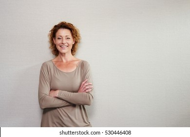Portrait of older woman smiling with arms crossed by wall
