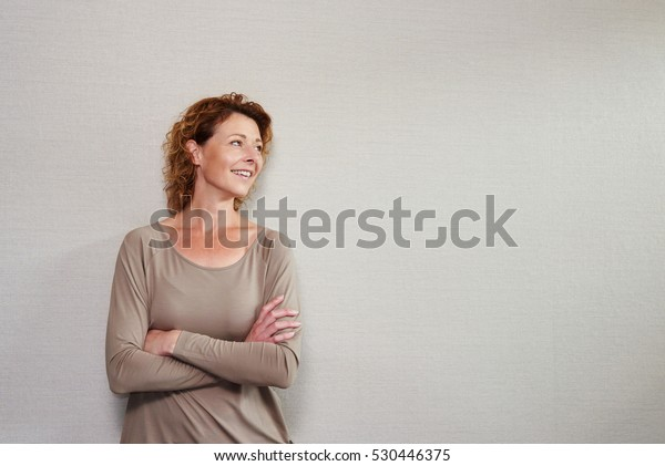 Portrait of older woman standing with arms crossed looking away smiling