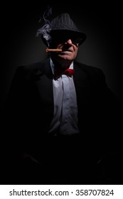 Portrait of omerta boss with cigar and glasses.